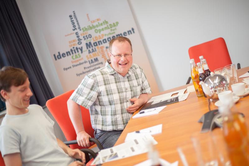 Foto: Mitarbeiter vor Identity Management Wortwolke