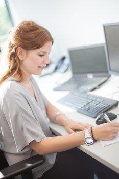 Foto: Mitarbeiterin macht sich Notizen